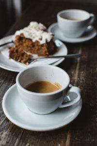 zdjęcie-dwóch-filiżanek-kawy-z-porcją-ciasta-marchewkowego