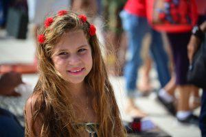 zdjęcie uśmiechniętej dziewczynki z kwiatami we włosach