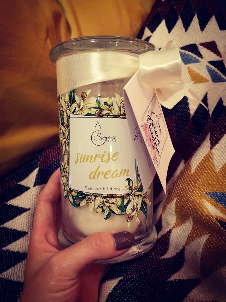 świeczka z biżuterią na tle poduszki